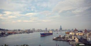 在高雄港(高熊,台湾)的一个帆船和城市视图 免版税库存图片