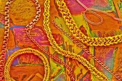 在高雅丝绸背景的时髦金链子 免版税图库摄影