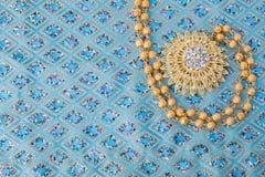 在高雅织品的发光的金首饰 免版税库存照片