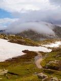 在高高山山,在黑暗的重的云彩下的多雪的蓝色峰顶的晚上 免版税库存照片