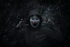 在鬼的树的可怕邪恶的小丑穿戴在附近的夹克和森林 免版税库存照片