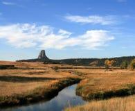 在魔鬼塔在休利特附近和圣丹斯怀俄明前面的草甸小河在黑山附近 图库摄影