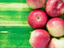 在鲜绿色的木背景桌上的成熟水多的红色苹果, 免版税库存照片