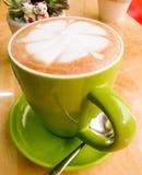 在鲜绿色的杯子的拿铁咖啡在一张木桌上 图库摄影