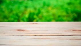 在鲜绿色的树背景的木桌在defocus的 库存图片