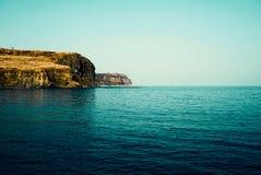在鲜绿色的海水附近的岩石海岸线 免版税库存照片