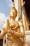 在鲜绿色菩萨,曼谷玉佛寺寺庙的金黄Kinnari雕象  免版税库存照片