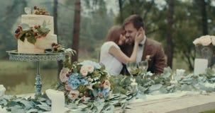 在鲜美蛋糕、花束、蜡烛和叶子的特写镜头视图在被弄脏的背景的桌上爱恋美丽 股票录像