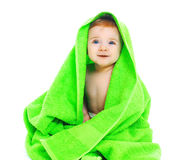 在鲜绿色的毛巾下的逗人喜爱的微笑的婴孩 免版税库存照片