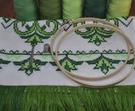 在鲜绿色的threa的十字绣绣花绷木毛巾 免版税库存图片