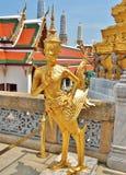 在鲜绿色菩萨,泰国的寺庙的一个金黄Kinnara雕象 免版税库存图片