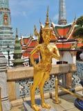 在鲜绿色菩萨,泰国的寺庙的一个金黄Kinnara雕象 图库摄影