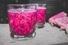 在鸡尾酒杯的红色龙果汁与Bokeh或迷离作用背景 库存图片