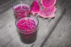 在鸡尾酒杯的红色龙果汁与Bokeh或迷离作用背景 免版税库存照片