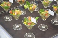 在鸡尾酒马蒂尼鸡尾酒玻璃的食物 免版税库存图片