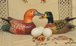 在鸭子旁边的复活节白鸡蛋在米黄背景 库存图片