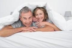 在鸭绒垫子下的快乐的夫妇 免版税库存图片