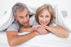 在鸭绒垫子下的愉快的夫妇 免版税库存图片