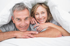 在鸭绒垫子下的爱恋的夫妇 库存照片