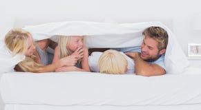 在鸭绒垫子使用下的愉快的家庭 免版税库存照片
