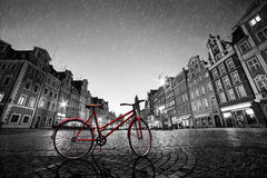 在鹅卵石历史的老镇的葡萄酒红色自行车在雨中 波兰wroclaw 免版税库存照片