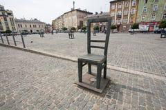 在鹅卵石街道上的巨型的椅子 图库摄影