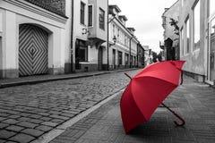在鹅卵石街道上的红色伞在塔林老镇 库存照片