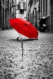 在鹅卵石街道上的红色伞在老镇 风和雨 免版税库存照片