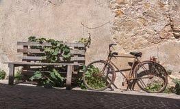 在鹅卵石街道上的被放弃的自行车 免版税库存照片