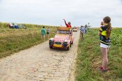在鹅卵石路环法自行车赛的Cochonou有蓬卡车2015年 库存照片