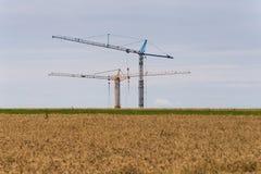 在麦地后的建筑用起重机在很远天际 库存照片