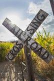在麦地附近的古色古香的国家路轨平交道口标志 库存照片