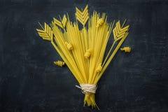 在麦子在黑石背景的耳朵花束的构成安排的未煮过的意粉Penne面团 菜单海报模板 库存照片