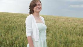 在麦子的高绿色小尖峰的中美丽的少女在领域的 享受夏天,和谐的年轻愉快的妇女人和 影视素材
