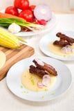 在麦片粥玉米奶油床上的猪肉ribbs 图库摄影