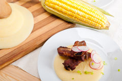 在麦片粥玉米奶油床上的猪肉ribbs 库存图片