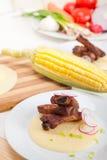 在麦片粥玉米奶油床上的猪肉ribbs 免版税库存照片
