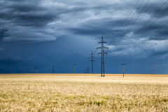 在麦田和电定向塔的巨大的雷云 库存照片