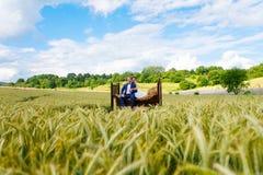 在麦田的愉快的婚礼夫妇 免版税库存照片