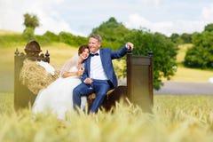 在麦田的愉快的婚礼夫妇 免版税图库摄影