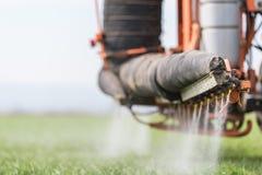 在麦田的拖拉机喷洒的杀虫剂与喷雾器 库存照片