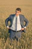 在麦田的年轻农夫商人 图库摄影