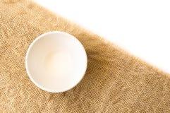 在麻袋布和白色backgro的特写镜头顶视图空的白色碗 库存照片