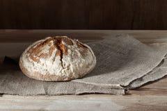 在麻袋布的圆的麦子黑麦面包在木背景 库存照片