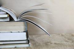 在麻袋布的老课本堆与在上面的书转动的页 库存照片