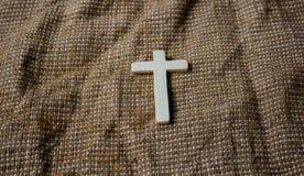 在麻袋布背景的木十字架 库存照片