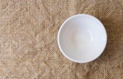 在麻袋布背景textur的特写镜头顶视图空的白色碗 库存图片