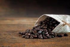 在麻袋布袋子的咖啡豆在木桌上 免版税库存照片
