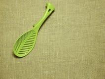 在麻袋布被编织的背景的绿色塑料杓子 库存图片