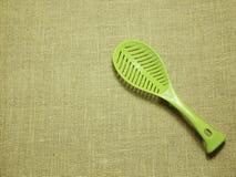 在麻袋布被编织的背景的绿色塑料杓子 免版税库存图片